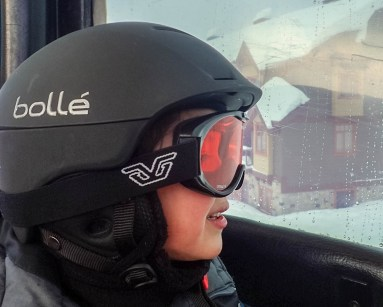 Young boy in ski helmet and goggles looks out from a window - Learning to Ski at Kelowna's Big White