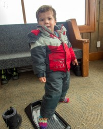 Young boy in snow suit on getting his feet measured - Learning to Ski at Kelowna's Big White
