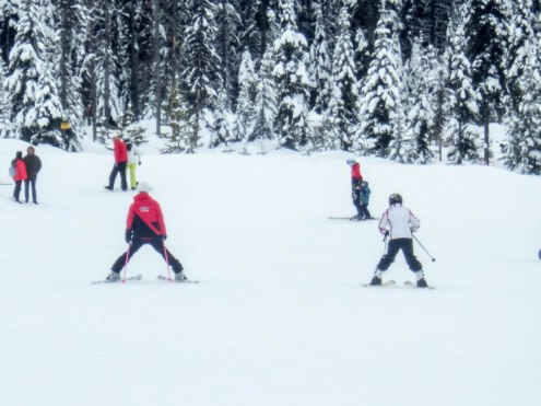 Woman takes ski lesson from an instructor - C gets his report card from his instructor at Big White