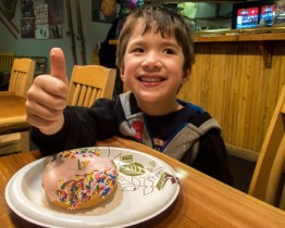 Young boy eating a donut gives a thumbs up - Learning to ski at Kelowna's Big White