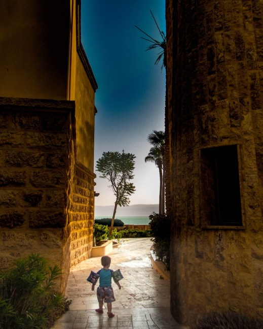 toddler wearing water wings walking between two tall buildings towards the Dead Sea at the Kempisnki Hotel