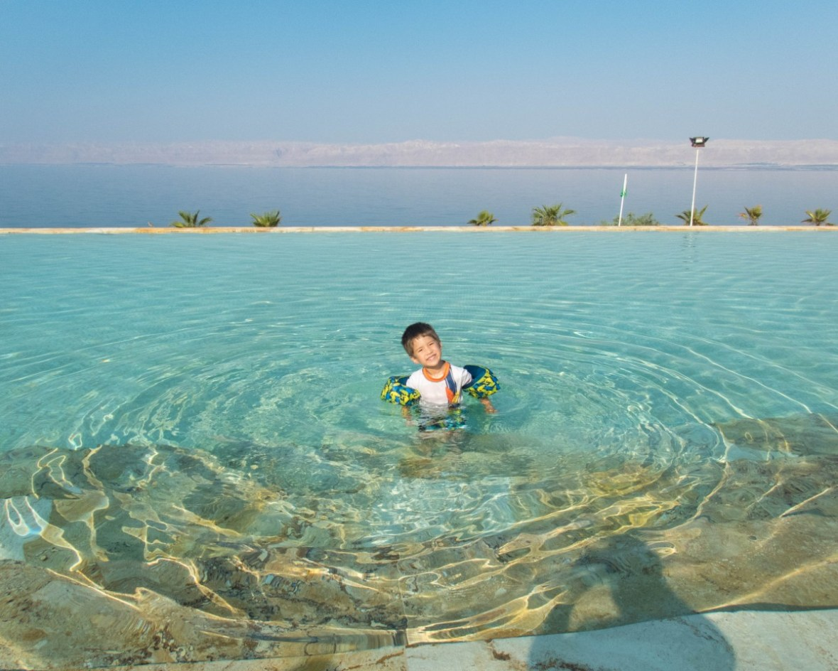 young boy smiles while in a pool with the Dead Sea in the background