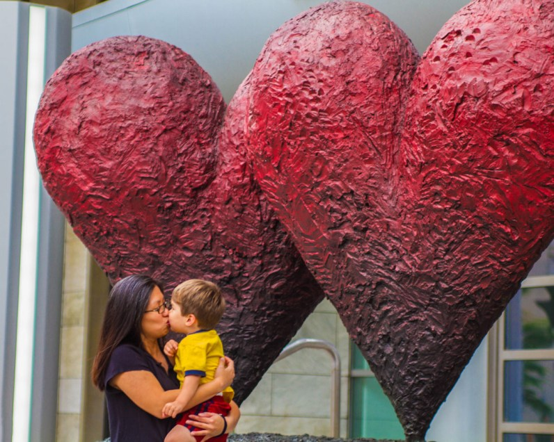 A mother and son share a kiss near heart sculptures in Quebec City on a road trip to Perce Quebec and Bonaventure Island