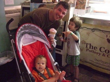 Father with two boys pose with their ice cream cones inside the Colonial Inn and Motel ice cream shop in Watkins Glen, New York.
