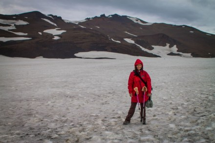 Woman in a red rain jacket smiles on a snow field with mountains in the background - Icelandic Highlands