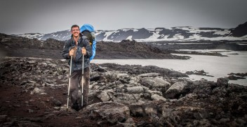 Man carrying infant in a kid-carrier standing on rocks and snow in the Icelandic Highlands