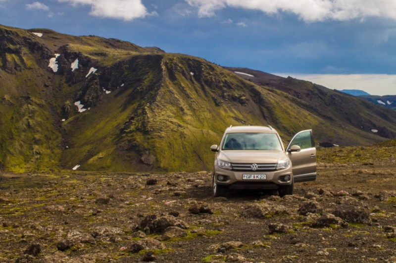 A volkswagen tiguan sits on rough ground with green hills in the background - Icelandic Highlands