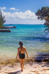 A woman wearing a bathing suits walks into crystal clear in a small cove in Bermuda - Boating in Bermuda