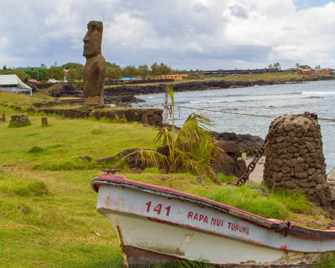 A small fishing boat sits on the green grass next to the ocean with a moai sculputre and a small town in the background