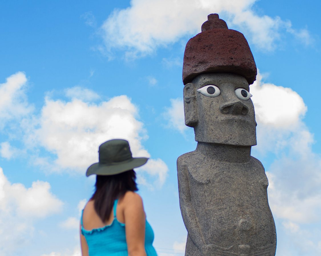 Woman wearing a green hat and blue shirt looks up at a completed replica sculpture of a moai backed with a blue sky on Easter Island