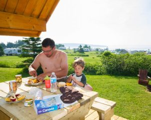 Dad prepares sandwiches for son on a picnic table with a view of the National Park of Bonaventure Island and Perce Rock.
