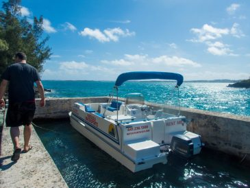 Man walks along a dock towards a pontoon boat - Boating in Bermuda