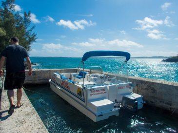 Man walks along a dock towards a pontoon boat - Boating in Bermuda