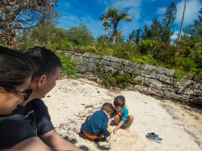 Two parents watch their children playing in the sand on the beach - Boating in Bermuda