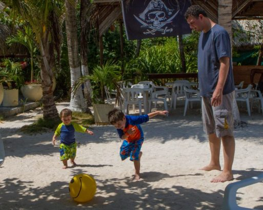 Boys playing soccer with a beach ball in the sands of Pirate Island while man watches.