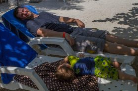 Man and boy lay down on their own lounge chairs in the sand on Pirate Island.