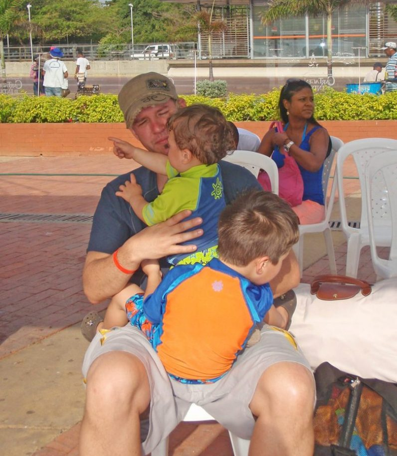 Father with two boys on his lap waiting at the pier for their boat to Pirate Island.