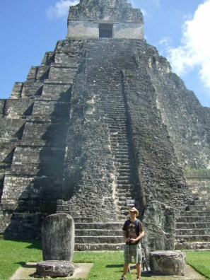 A traveler stands in front of a tall Mayan pyramid on a grassy field.