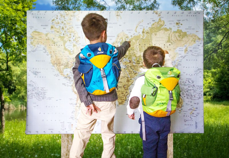Two young boys in sweaters wearing cute bird backpacks stand in a forest and point at places on a world map