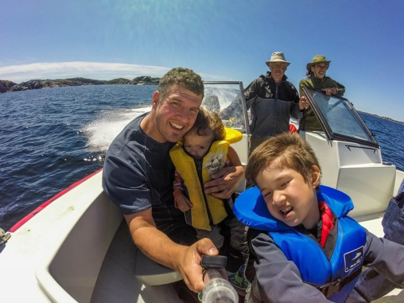 A dad take a picture of him and two young boys while boating alongside icebergs - Icebergs in Twillingate