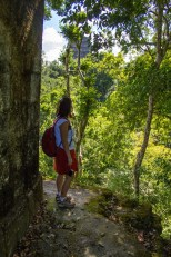 An asian woman in a backpack explores the ruins in the forests of Tikal