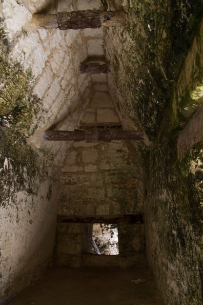 Inside a long narrow room with wooded braced arched roofs that made up dwellings of a Mayan ruin