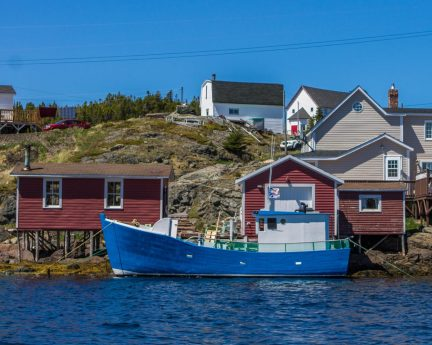 a cute fishing village in Newfoundland with colour houses on a rising rocky hill and a large fishing boat in the waters - Icebergs in Twillingate