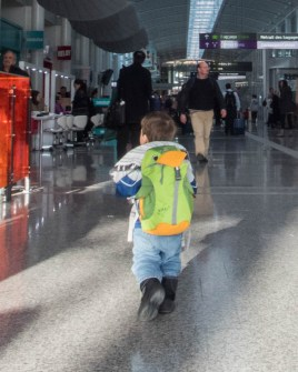 A toddler carrying a backpack walks through an airport