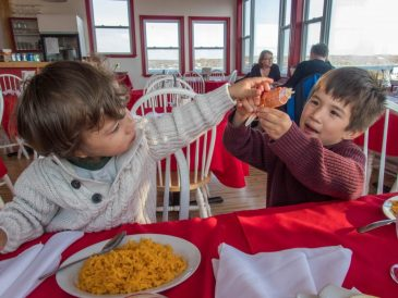 Two children playing with crab claw at Lightkeeper's Seafood Restaurant.