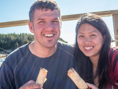 A man and woman sit on a patio and get ready to eat some spring rolls - Icebergs in Twillingate