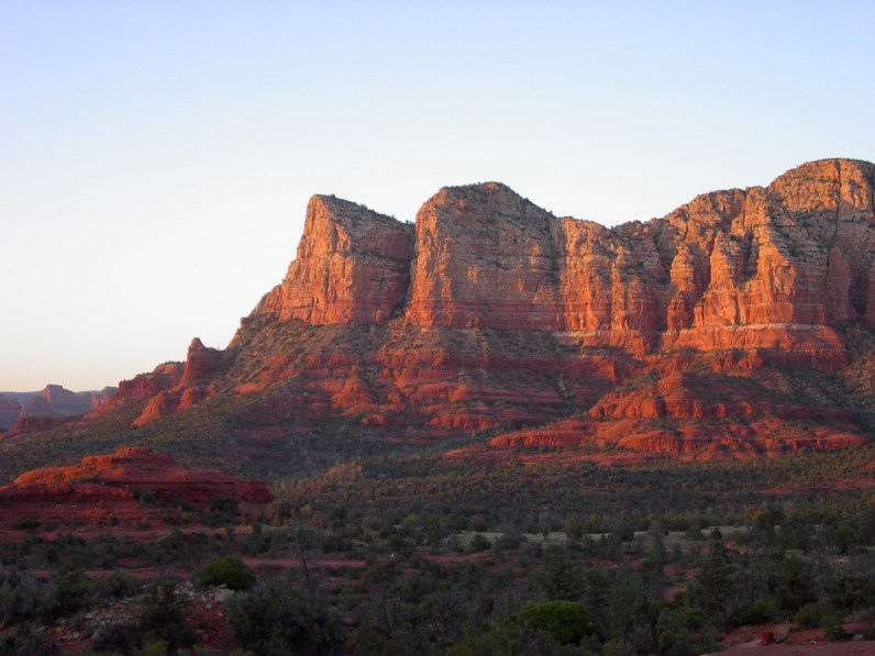 The setting sun lights up the rocky cliffs of Sedona Utah with brilliant colours - things to see in the American Southwest