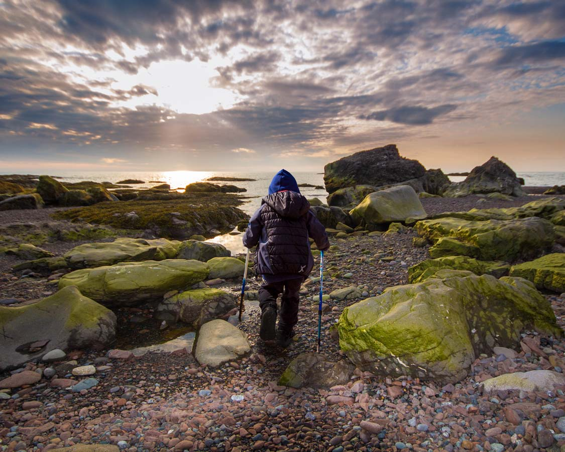 Boy Hiking Green Gardens in Gros Morne National Park at Sunset
