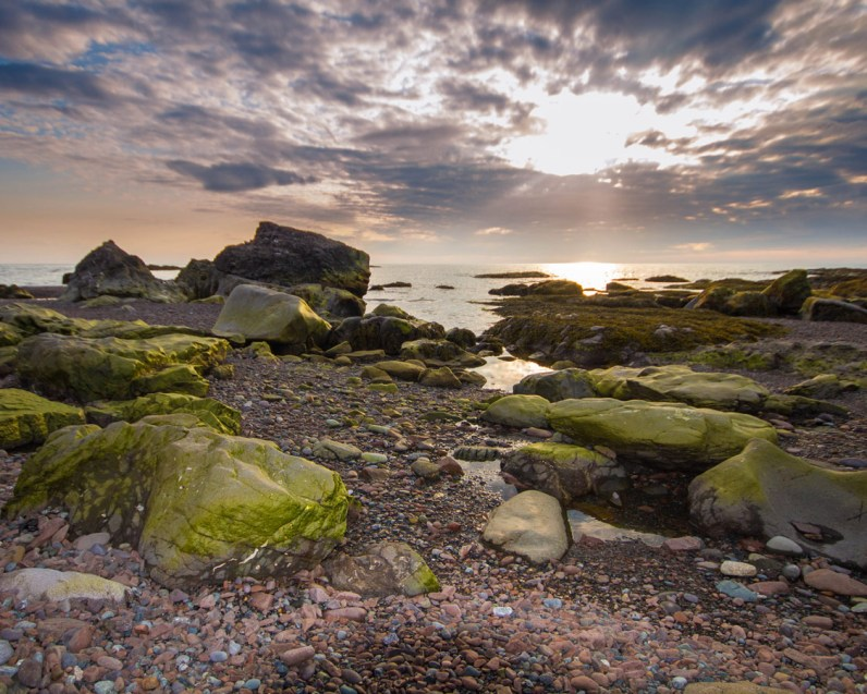 Rocks covered in green moss line the coast of Newfoundland with a spectacular sunset as a backdrop - Hiking Green Gardens in Gros Morne National Park