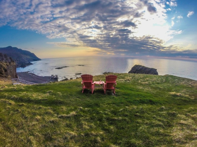 two red muskoka chairs sit on green grass on a cliff overlooking the ocean in Gros Morne National Park - Hiking Green Gardens in Gros Morne National Park