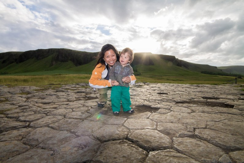 A mother and young boy smile on honeycomb shaped rocks - An Epic 14 Day Iceland Itinerary
