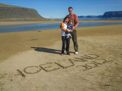 A young family stands on a beach in Iceland with Iceland 2012 written in the sand - An Epic 14 Day Iceland Itinerary