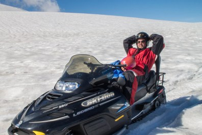 A young boy sleeps on his fathers lap on a snowmobile driving across a glacier - An Epic 14 Day Iceland Itinerary