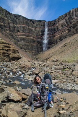 A woman and a sleeping child in a kid-carrier sit below a waterfall - An Epic 14 Day Iceland Itinerary
