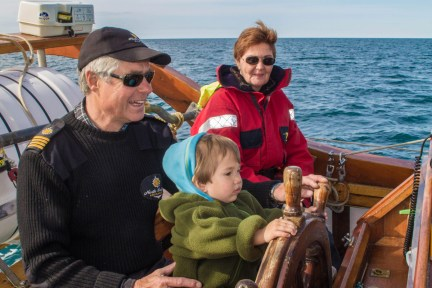 A young boy sits on a captains lap on a schooner - An Epic 14 Day Iceland Itinerary