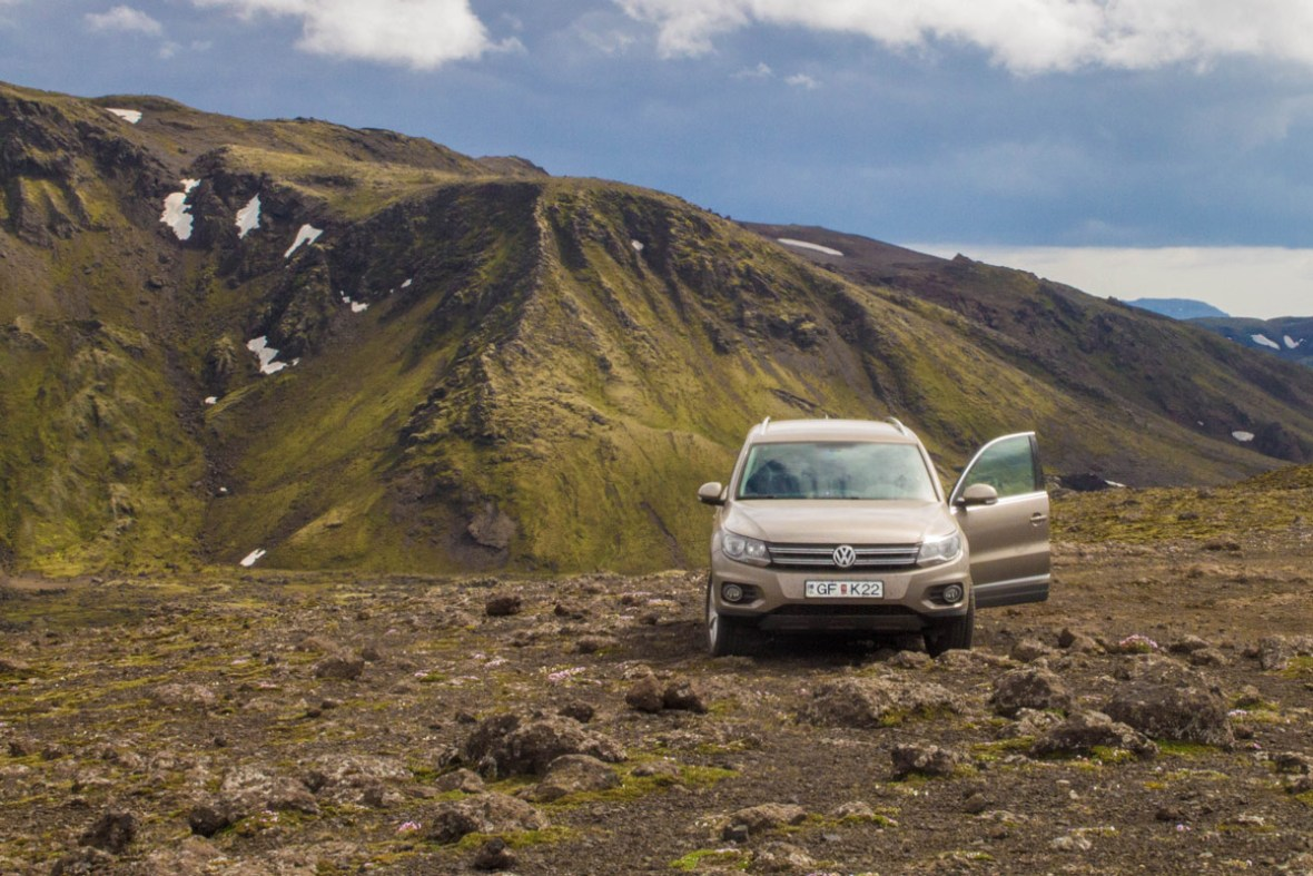 An SUV sits on rocky ground near a mountain - An Epic 14 Day Iceland Itinerary