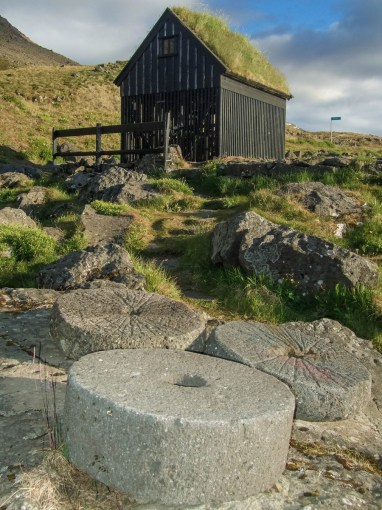 Large stone wheels lie on the ground near a Viking style fishing hut on the coast of Iceland - An Epic 14 Day Iceland Itinerary