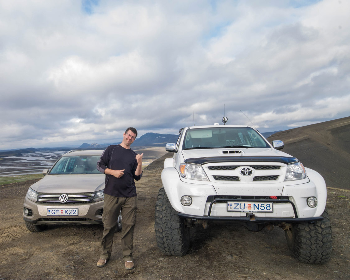 A man standing next to a small SUV on a dirt road laughs beside a Monster truck - An Epic 14 Day Iceland Itinerary