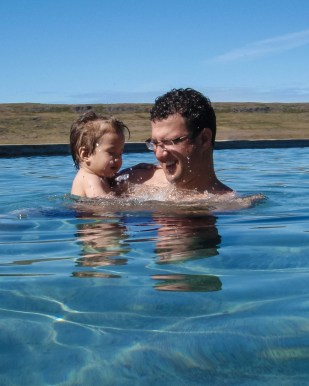 A father and son splash around in a natural pool in Iceland - An Epic 14 Day Iceland Itinerary