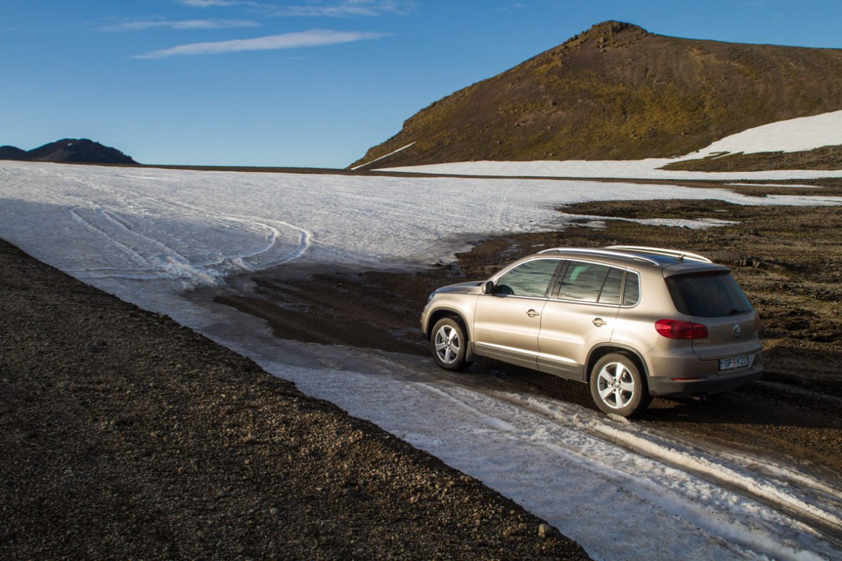 An SUV stopped at a spot where a glacier washed over a road - An Epic 14 Day Iceland Itinerary