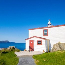 Two young children knock on the door of a lighthouse