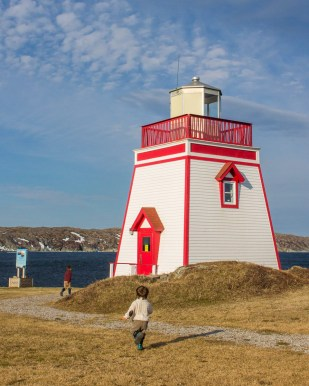Two young boys race towards a small red and white lighthouse in Newfoundland - Newfoundland Viking Trail