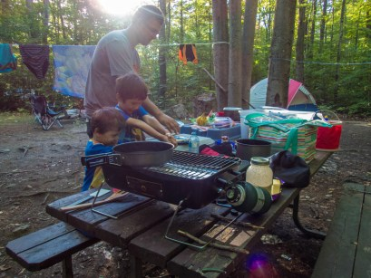 A fatehr and two young boys make food at a campground picnic table - Top things to do in Bon Echo Provincial Park