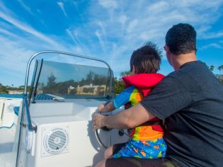 Father and son on boat in Bermuda in search for the best Bermuda beach