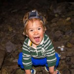 A toddler wearing a headlamp smiles happily inside a cave - caves you can visit with kids