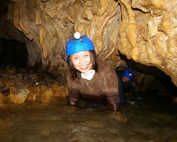 A woman wearing a hard hat and headlamp emerges from the water inside a cave - caves you can visit with kids